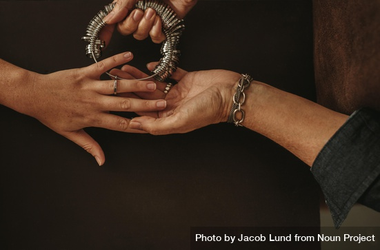 Closeup of woman checking ring size of female hand in jewelry shop by Jacob Lund Photography from Noun Project